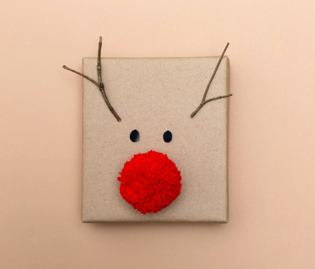 Red nose reindeer gift box on a light brown background