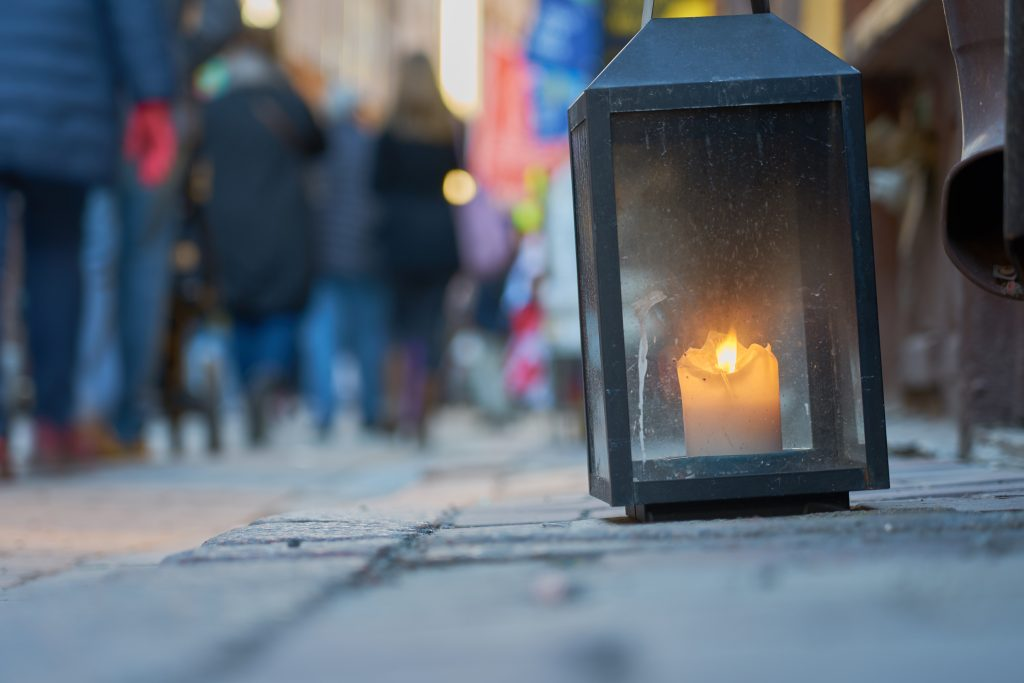 Big metal dirty lantern with burning candle inside, outdoor on a ground with blurred crowded street on a background.